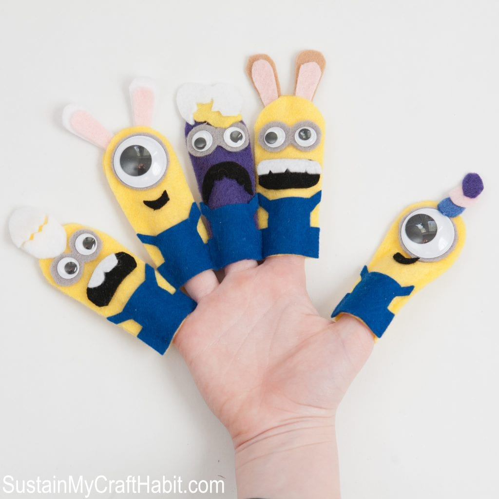 Five Minions finger puppets on the hand of a child against a white background.