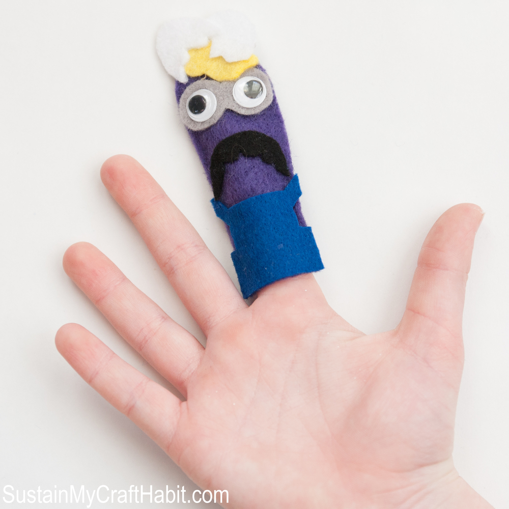 Purple minion felt finger puppet on a child's open hand