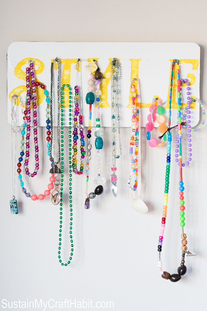 An accessory organizer holding necklaces and bracelets.