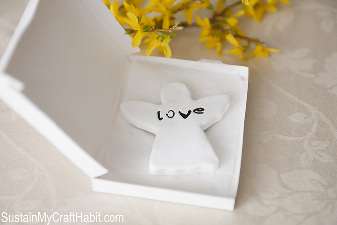 A small gift boxed filled with an angel-shaped ornament with the work love inscribed as a first communion favor idea