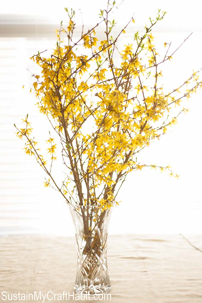 A crystal vase filled with blooming forsythia branches as a first communion party idea
