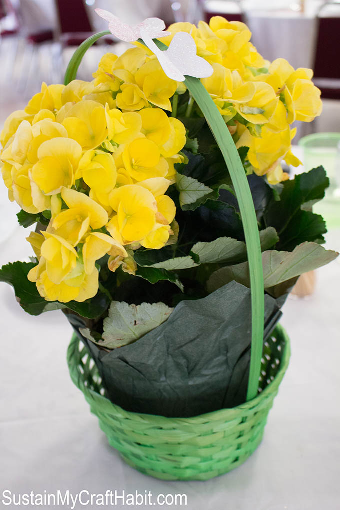 Yellow potted begonias in a green wicker basket as first communion centerpiece idea