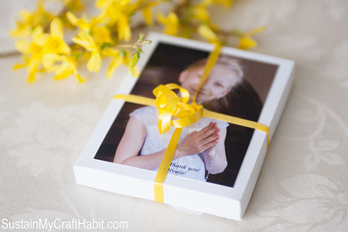 Photo of a little girl in her first communion dress attached to a gift box with a yellow ribbon
