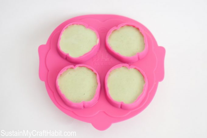 Green spinach smoothie with fruit poured into a brain shaped pink silicone mold