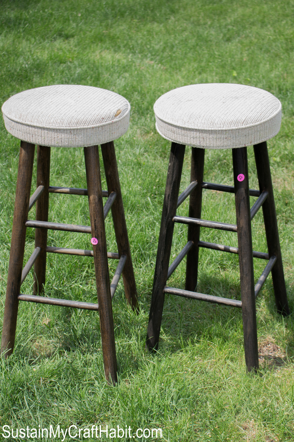 Two bar stools with dark brown legs and light fabric upholstery on the grass.