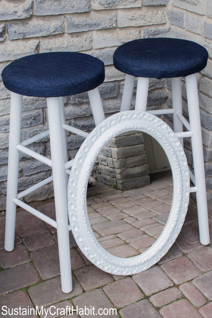 A painted mirror leaning against two upcycled bar stools outdoors on a stone patio.