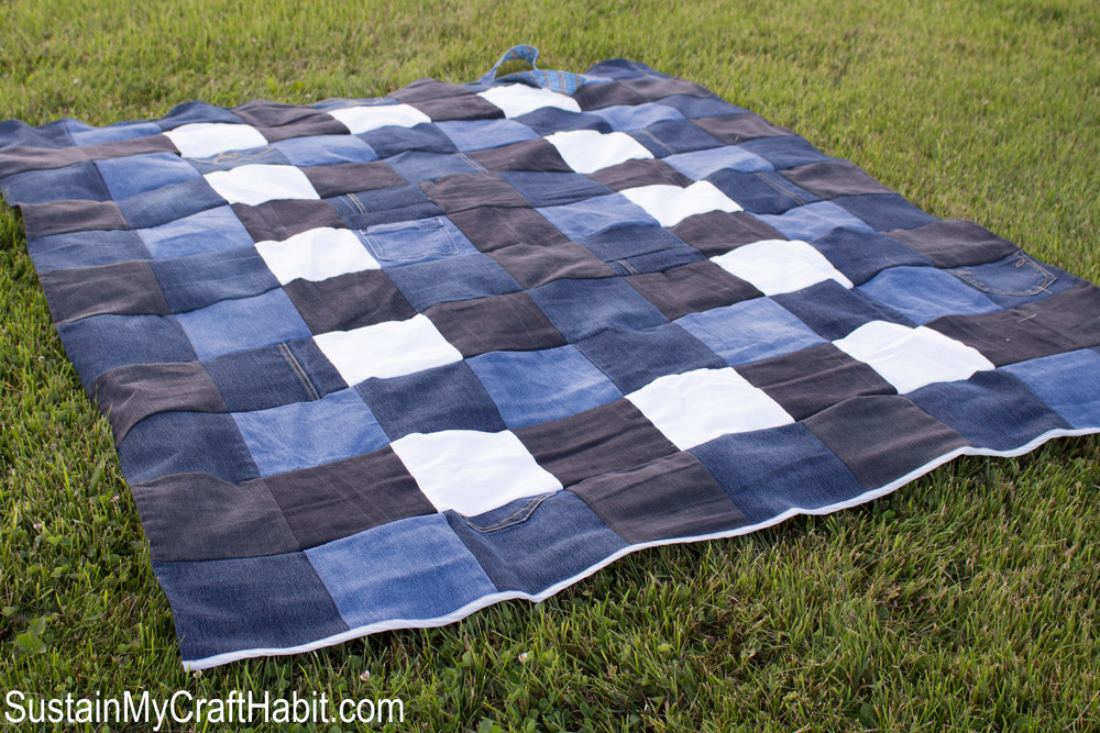 The DIY checkered denim picnic blanket laid out on the grass.