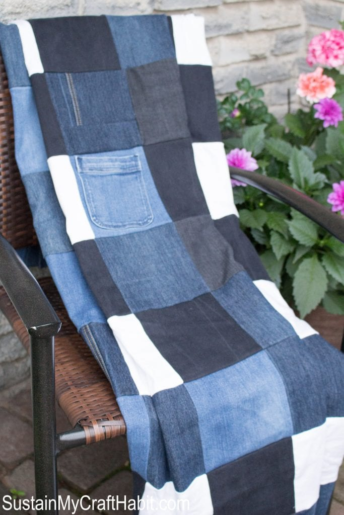 A checkered picnic blanket made from different colored denim, draped over a chair on a front porch. A basket of pink flowers are in the background.