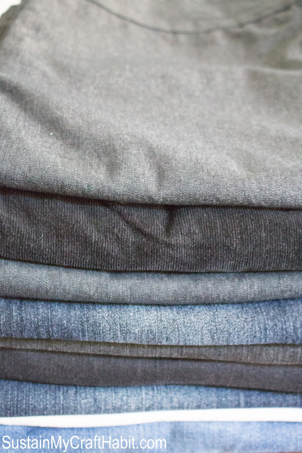 Close up view of a stack of old jeans showing different shades of blue and gray denim fabric.