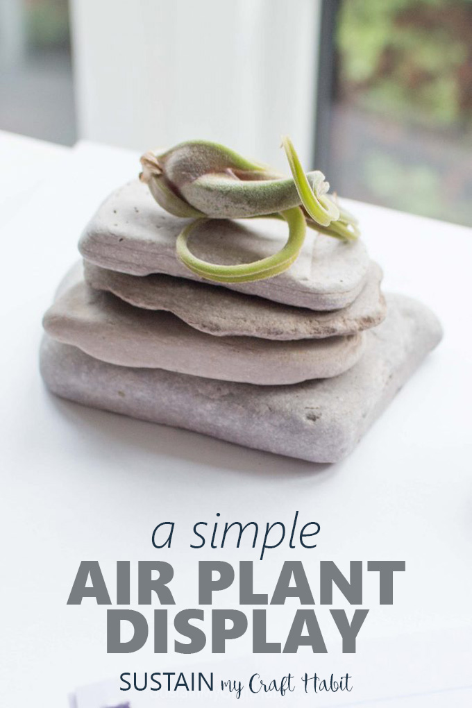 A stack of flat stones on a white office desk as an air plant display idea