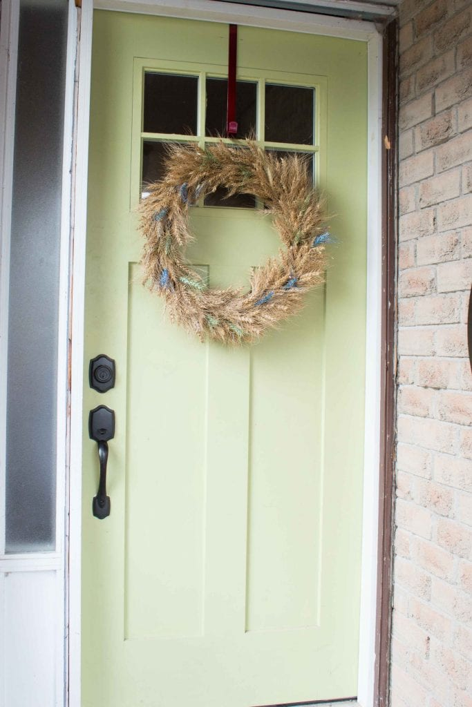 A DIY wheat wreath embellished with paint and glitter hanging on a lime green front door.