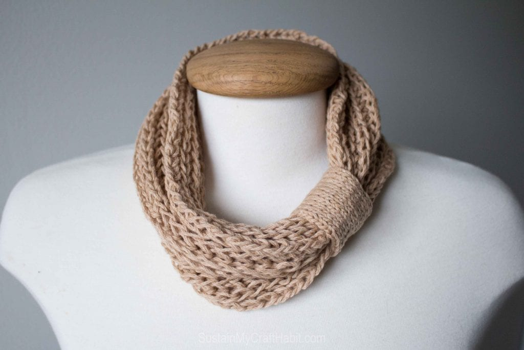 A tan colored knitted neck warmer made with a cowl knitting pattern on a manequin