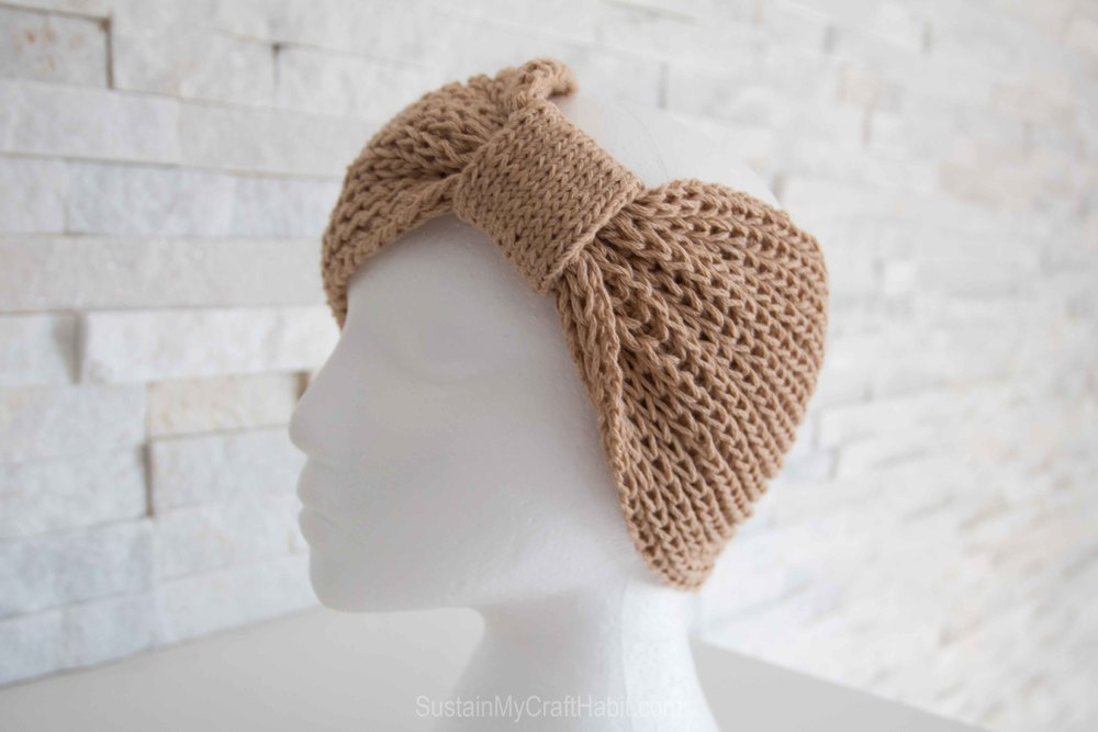 A knitted headband from a cowl knitting pattern on a mannequin head.