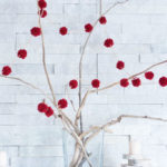 A DIY pom pom garland strung around driftwood branches as a part of a rustic Christmas mantel decorating idea