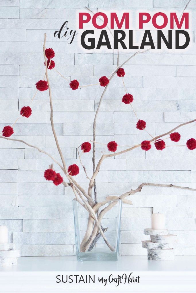 Red DIY pom pom garland strung on branches in a vase on a fireplace mantel