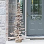 A rustic DIY driftwood Christmas tree on a front porch in front of a gray door