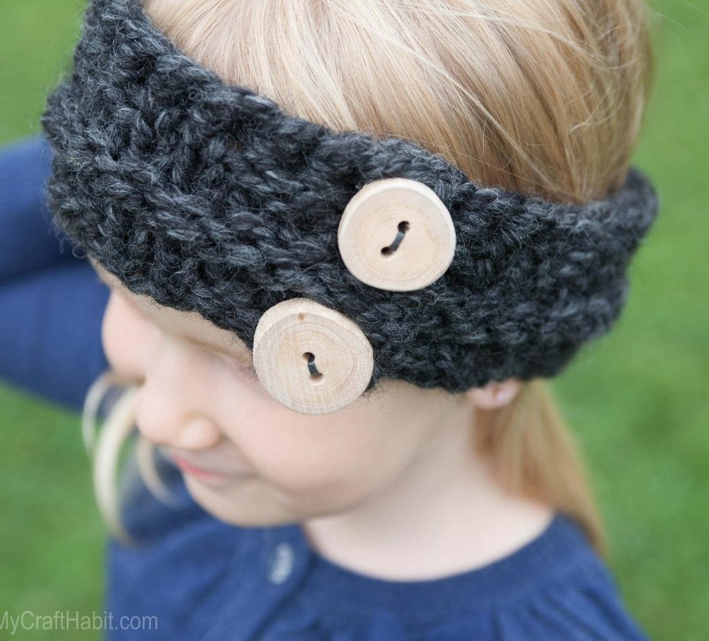 A child wearing a knitted headband made from a free pattern and embellished with handmade wood buttons