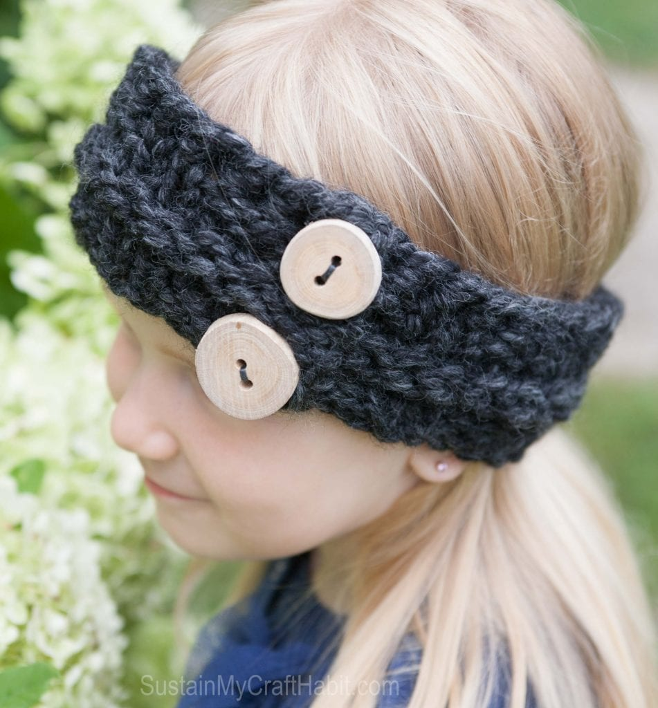 A blond child wearing a knitted headband pattern with handmade driftwood buttons
