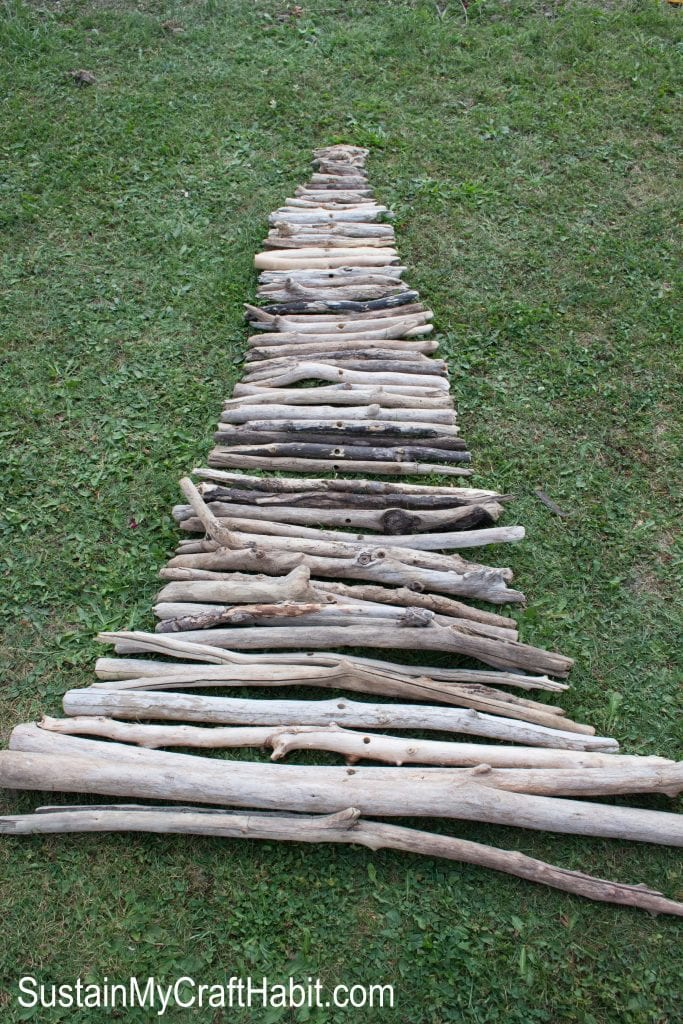Lining up different length of driftwood branches on the grass to make a Christmas tree shape