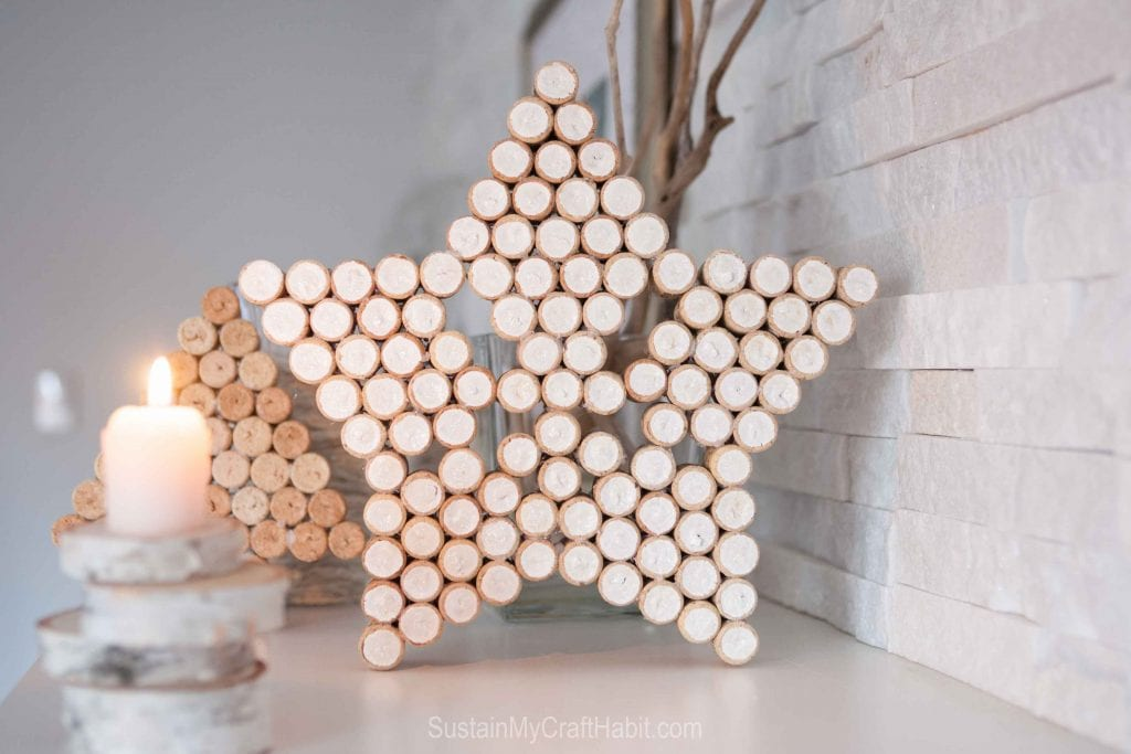 Wine cork craft ideas including a large star and wine cork Christmas tree on a neutral holiday mantle