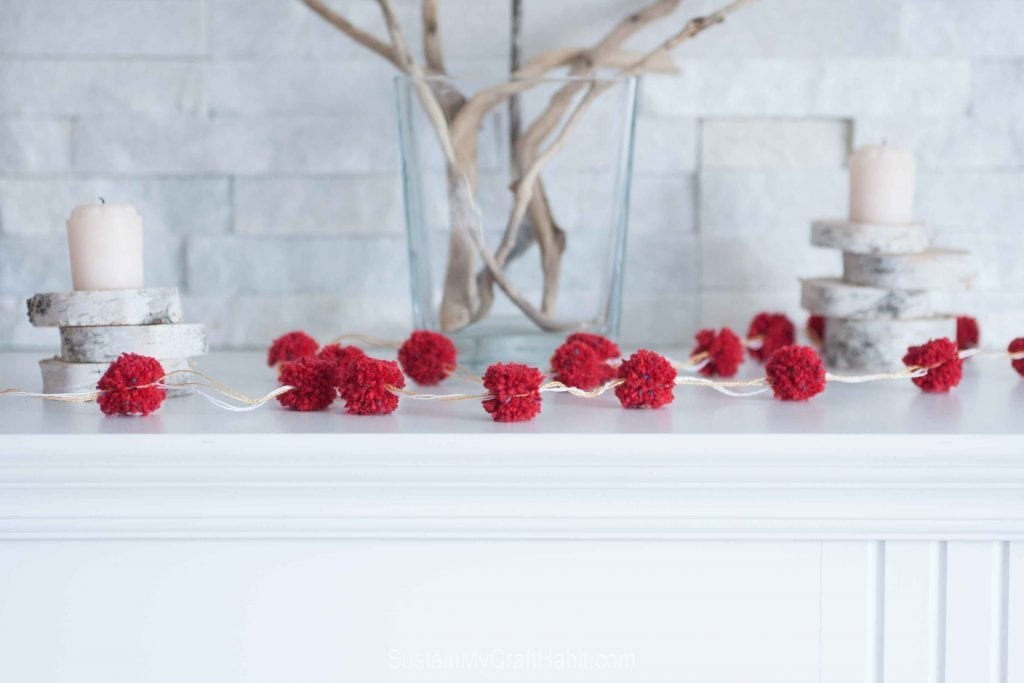 A red and white pom pom garland laid on top of a fireplace mantel with other rustic decorating elements