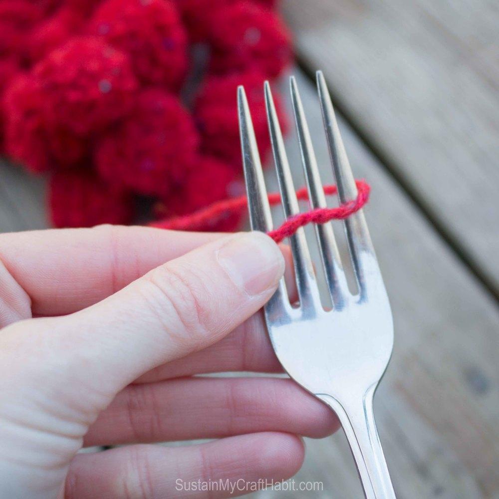 Winding red yarn around a fork to make a DIY pom pom