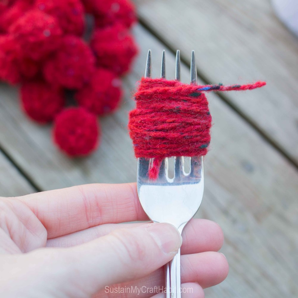 Red yarn would around a fork to create a DIY pom pom garland