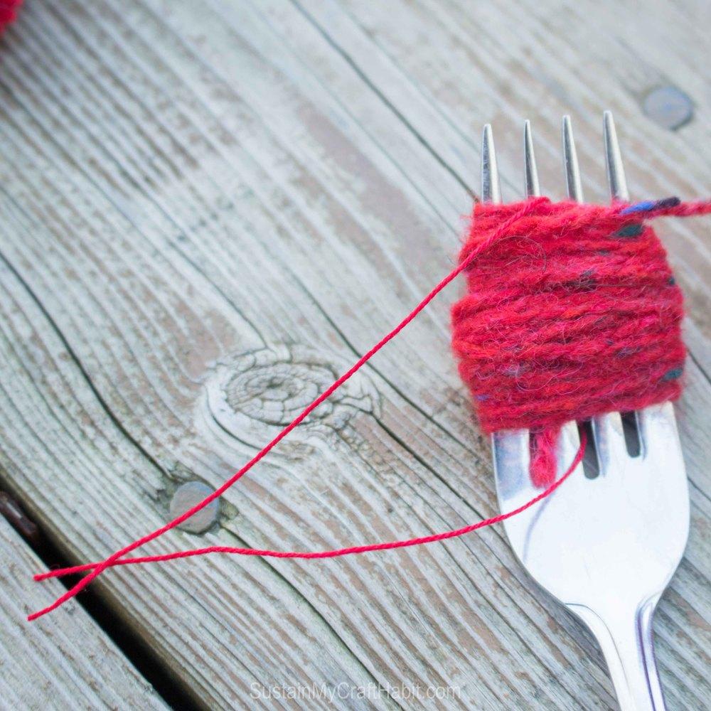 Tying would yarn around a fork to make a pom pom