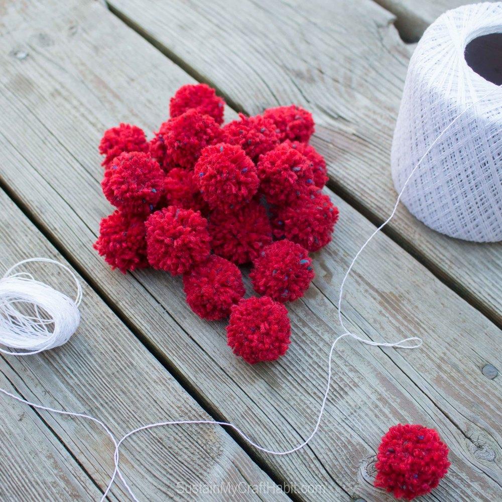 Attaching DIY pom poms together to form a garland