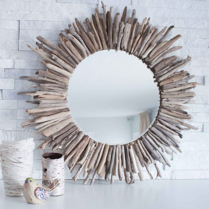 Large handmade driftwood mirror on a fireplace mantle with natural elements in front.