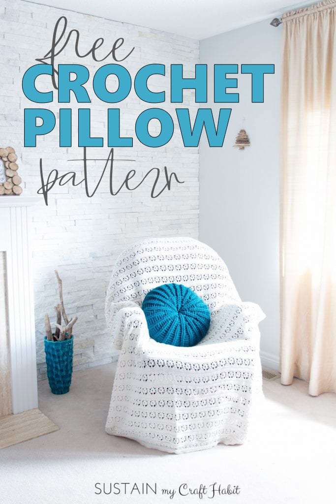 A teal, round crochet throw pillow on a chair covered with knitted white throw in the corner of bright white bedroom.
