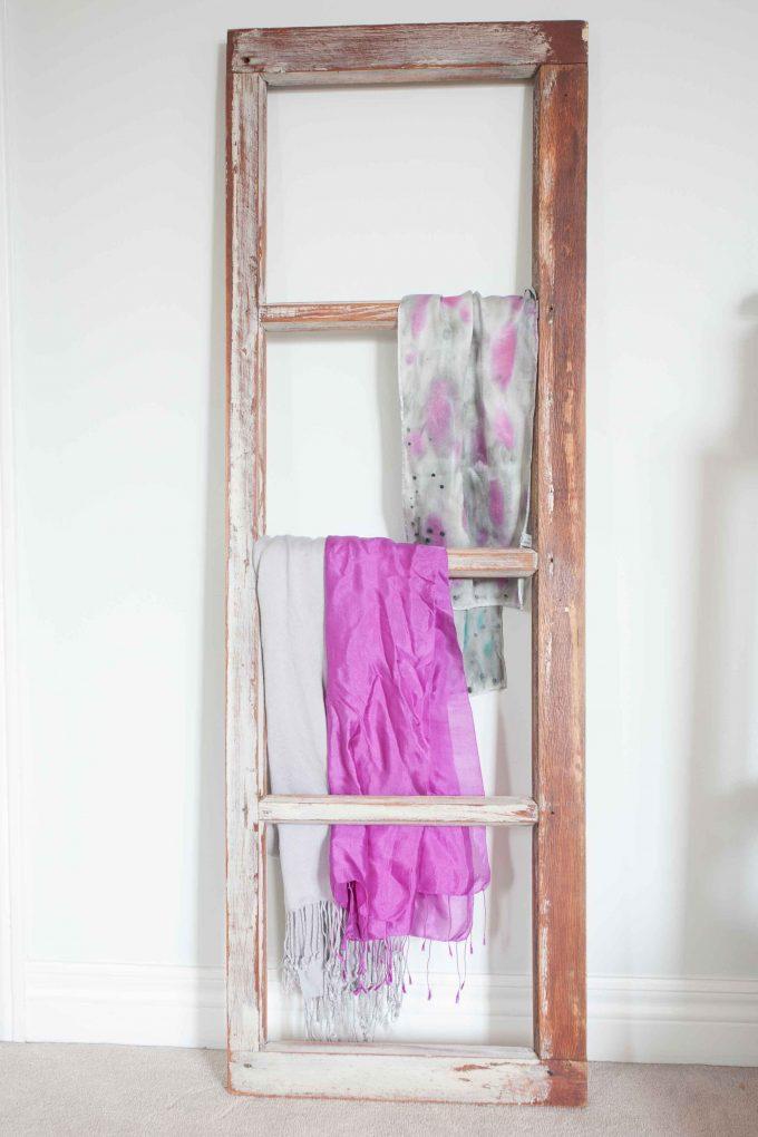 Old farmhouse window frame repurposed into a decorative scarf rack. #farmhousedecor