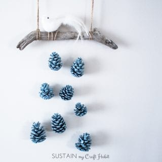 A beautiful bird perched above a cascading array of robin's egg blue pinecones makes a beautiful, inexpensive and easy rustic DIY wall art idea. Check out the detailed step-by-step tutorial.