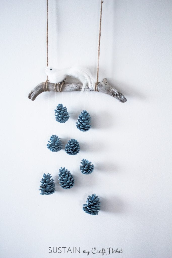 A beautiful bird perched above a cascading array of robin's egg blue pinecones makes a beautiful, inexpensive and easy rustic DIY wall hanging idea. Check out the detailed step-by-step tutorial.