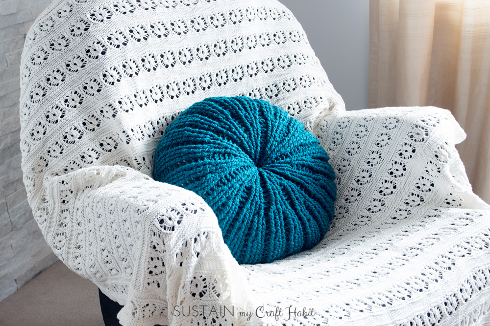 Completed sand dollar crochet pillow cover on a chair covered with a white knitted blanket