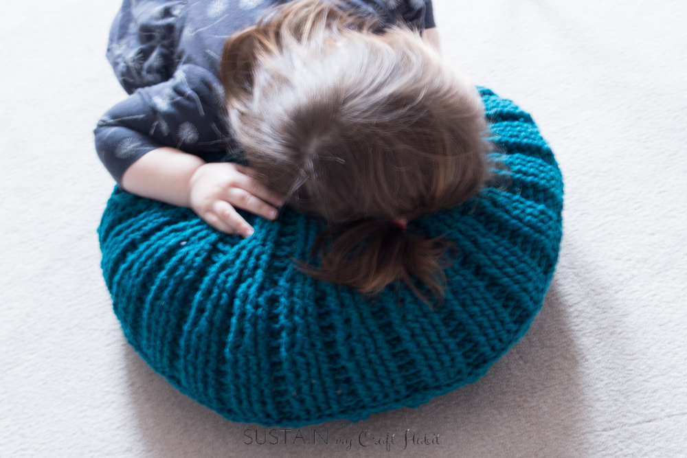 Baby laying with her head down on the pillow made with the free crochet pillow pattern made in the post