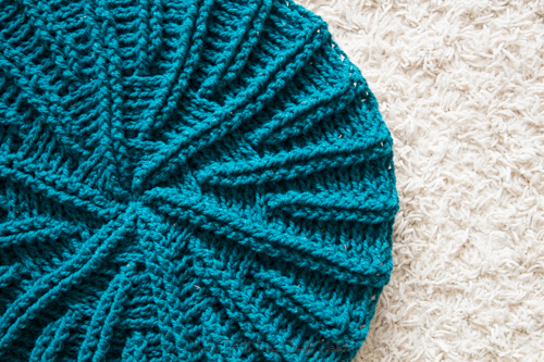 Image of the crochet pillow cover pattern made with teal wool yarn which looks like a sand dollar
