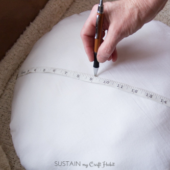 Measuring and marking the center of a round pillow form to create a pucker for the crochet pillow cover
