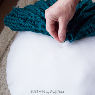 Poking the yarn through the center of the round pillow form for the crochet pillow cover