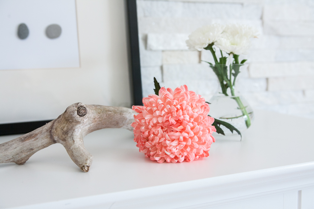 A coral chrysanthemum on a white fireplace mantel with a piece of driftwood and DIY wall decor in the background