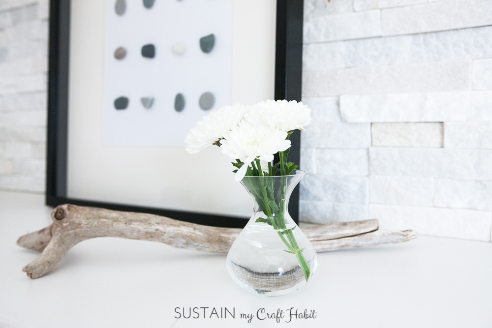 The DIY beach stone wall art on a white fireplace mantel with a piece of driftwood and small vase of fresh white mums