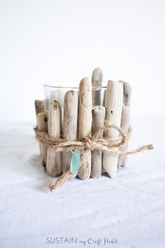 Small driftwood pieces glued onto a glass votive candle as a coastal decorating idea.