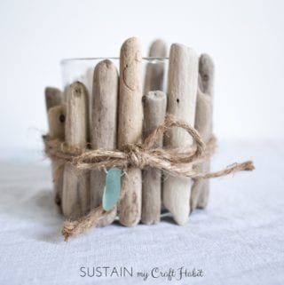 Glass votive candle embellished with rustic driftwood pieces on a white cloth surface