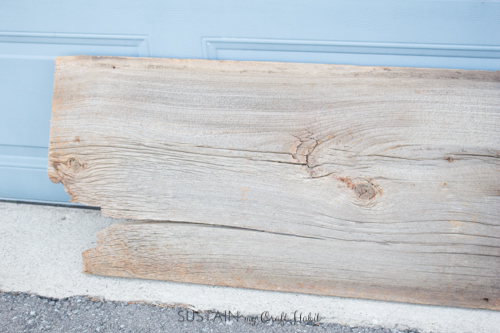 Close up image of one end of the piece of barn wood showing a large crack
