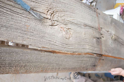 Prying off a splintered end of barn board to make a DIY console table