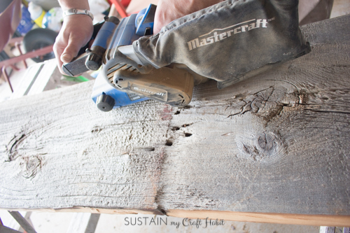 Sanding a piece of barn board with a belt sander