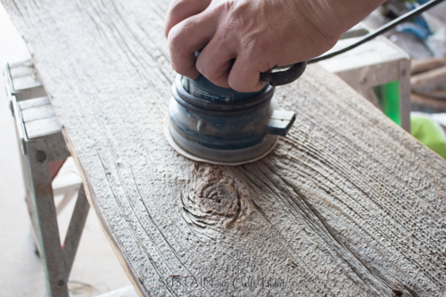 Sanding a piece of barn board with a palm sander