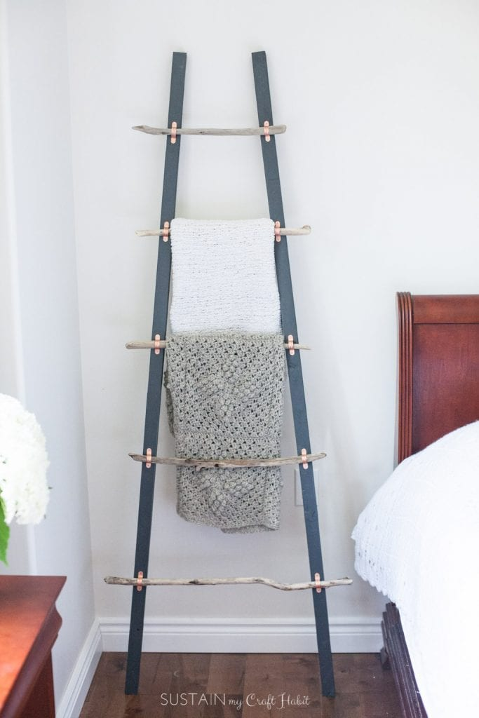 DIY driftwood blanket ladder leaning against a white wall in a bedroom.