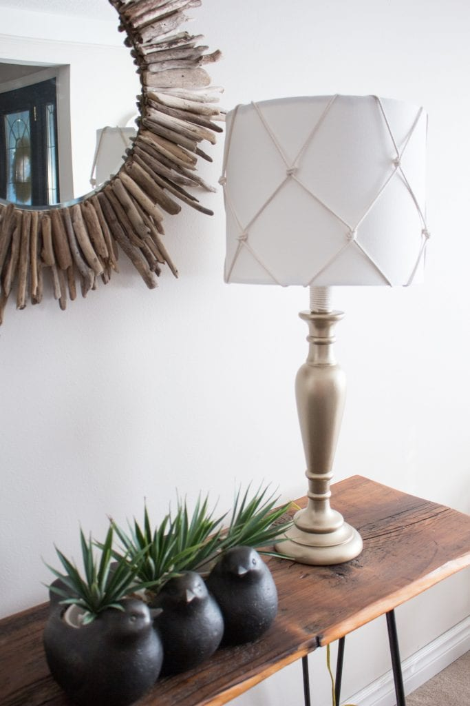 An made-over table lamp, with gold base and white nautical style shade sits on a rustic barn board console table in a living room.
