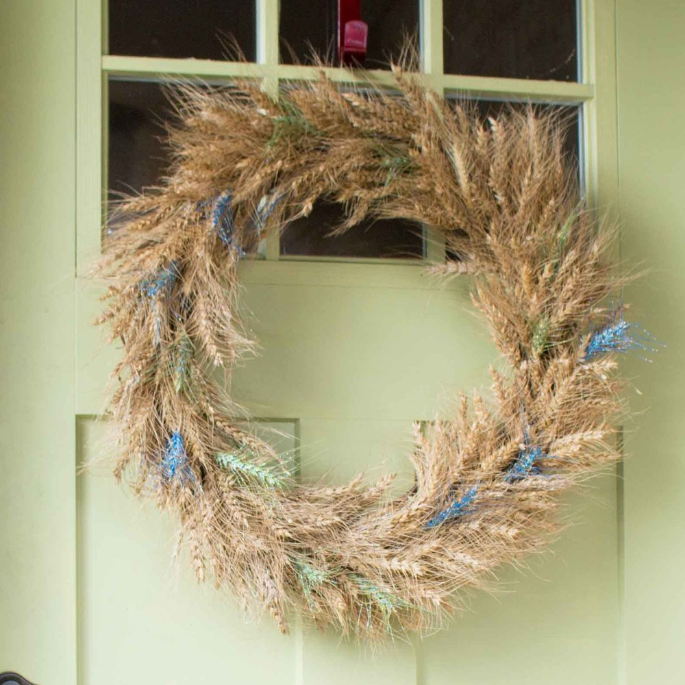 A DIY wheat wreath embellished with paint and glitter hanging on a green front door